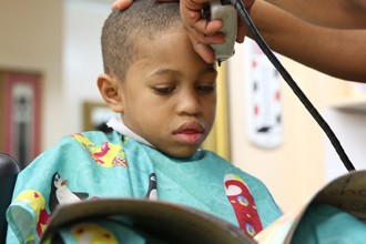 Una peluquería paga a los niños que leen mientras les cortan el pelo